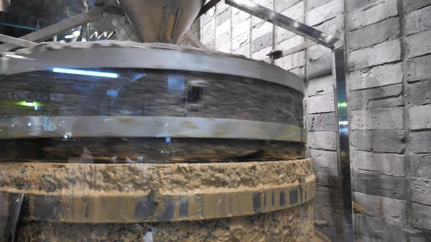 Machine grinding sesame seed, rotating stone quern, fresh tahini paste | Shutterstock HD Video #1054727771