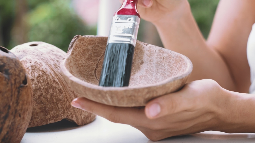 Close up of female hands brushing sanded coconut shells with oil. Woman crafting coconut candles on balcony   Shutterstock HD Video #1054727795