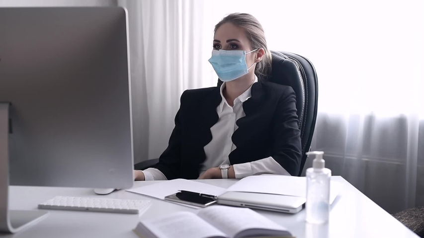 Work during self-isolation and quarantine. Young woman employee in a medical facial mask works in the office at the computer. Coronavirus Pandemic Covid 19. Royalty-Free Stock Footage #1054727912