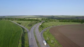 Aerial view on highway road through green fields on a summer sunny day. 4k footage of landscape with asphalt freeway between meadow and rural field. Drone shoots video of the countryside.