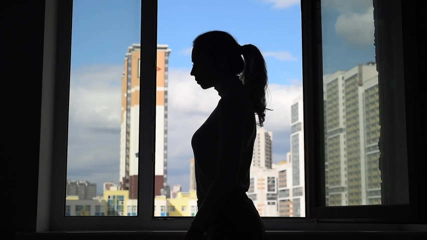 Epidemic Coronavirus Covid-19. Silhouette young woman at the window. Girl puts on a facial mask before going out. Life in quarantine self-isolation. Pandemic. Modern apartment buildings on background.