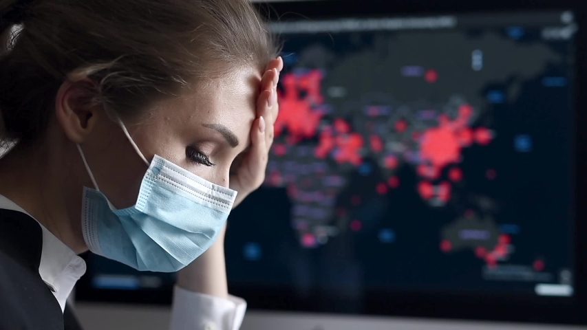 Side view close-up portrait of a young woman in disposable medical facial mask holding her head and looking at the epidemic map of the coronavirus Covid 19 pandemic on a computer | Shutterstock HD Video #1054728143