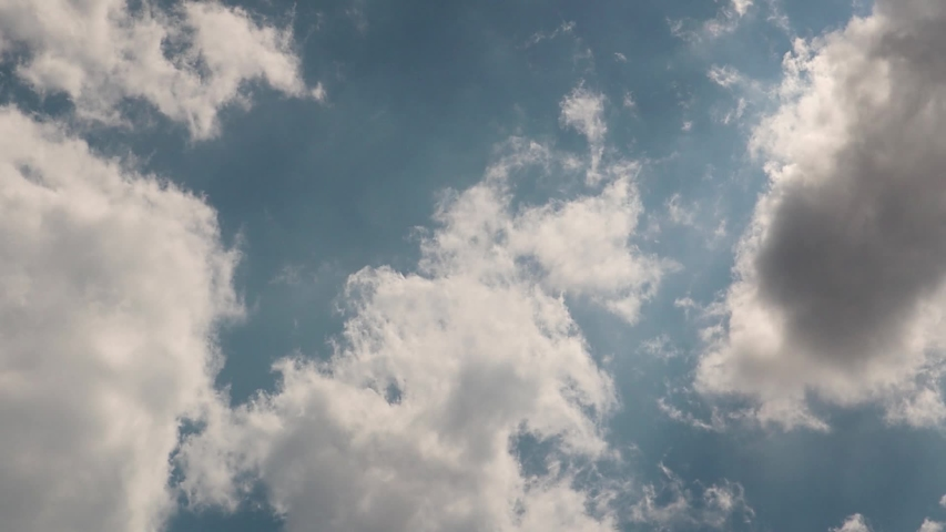 Background of bright blue sky and floating white clouds. Dramatic sky, weather before rain with gray gathering clouds | Shutterstock HD Video #1054728302
