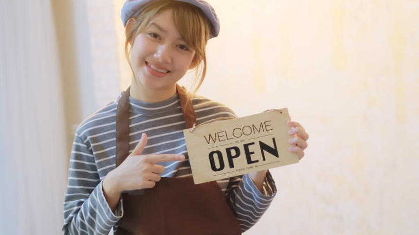 Business owner attractive young Asian woman in apron hanging we're open sign on front door smiling welcoming clients to new cafe. Beautiful Young Cafe Owner Turning Storefront Sign From Close to Open  | Shutterstock HD Video #1054728587