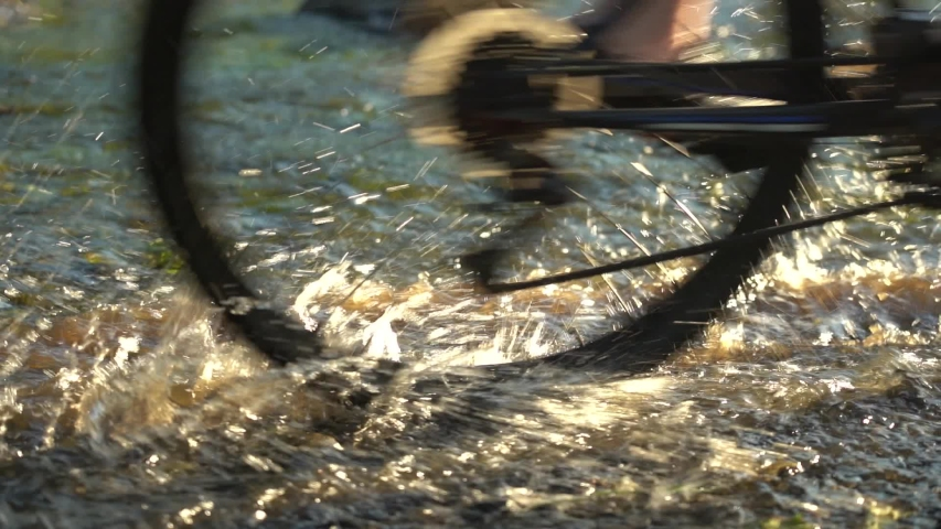 Cross the small mountain river on a mountain bike. The bike rides on the water. Spray from under the bicycle wheels. Shallow river in the rays of the setting sun. Slow motion, close-up, low angle, a | Shutterstock HD Video #1054728626