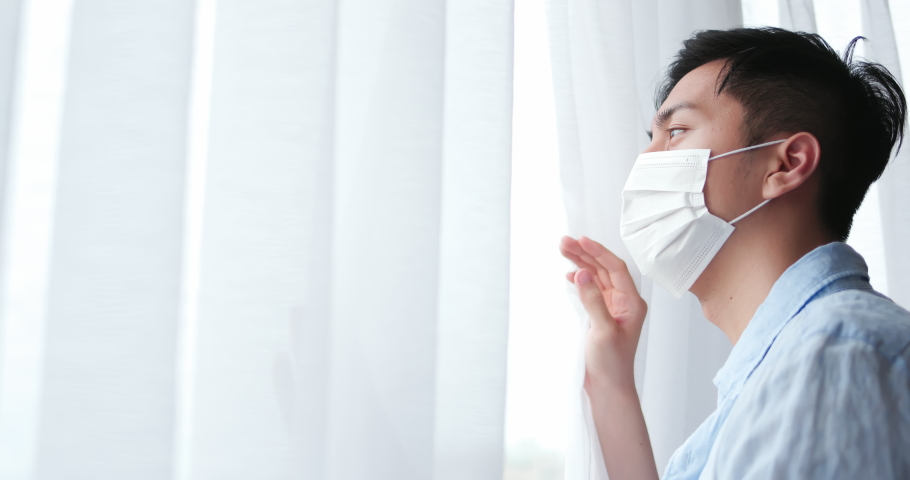 Asian young man with face mask stay isolation at home for self quarantine due to an epidemic of COVID-19 and he looks out by windows | Shutterstock HD Video #1054728869