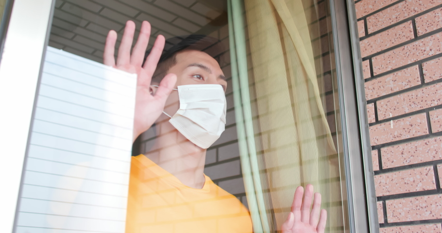 Asian young man with face mask stay isolation at home for self quarantine due to an epidemic of COVID-19 and he looks out by windows | Shutterstock HD Video #1054728872