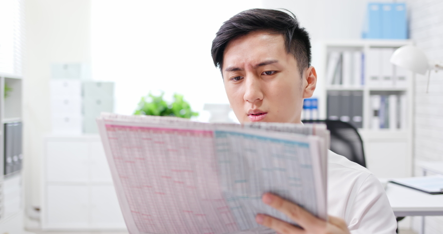 Asian young businessman is reading newspapers and shocked by unexpected fake news | Shutterstock HD Video #1054728893