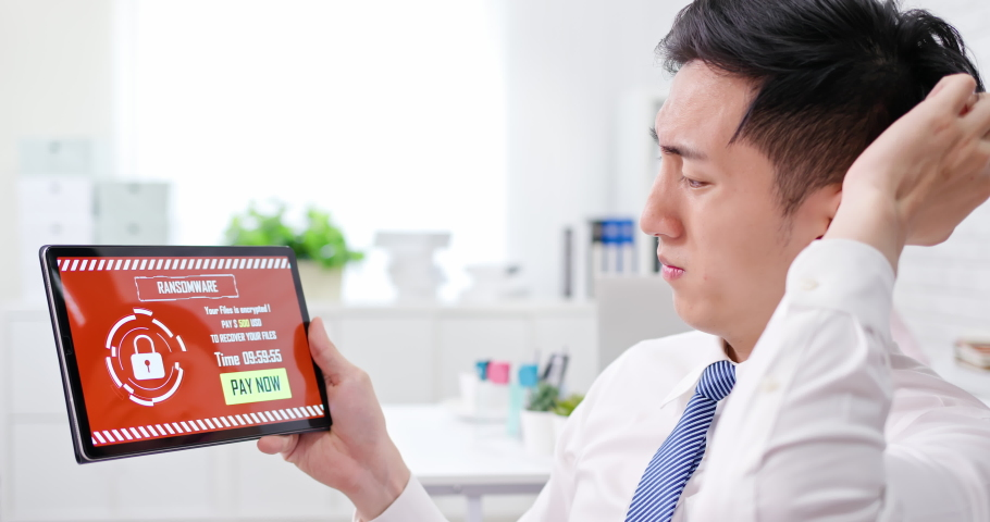 Asian worried young businessman looking at tablet pc with ransomware attack words on the screen in office | Shutterstock HD Video #1054728902