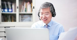 telework concept - Asian senior businessman use computer and headphone microphone to join a video meeting in the office