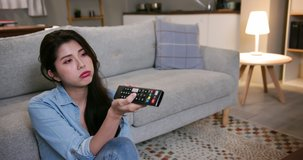 asian young woman is watching tv and feel bored sitting on the floor in living room at home