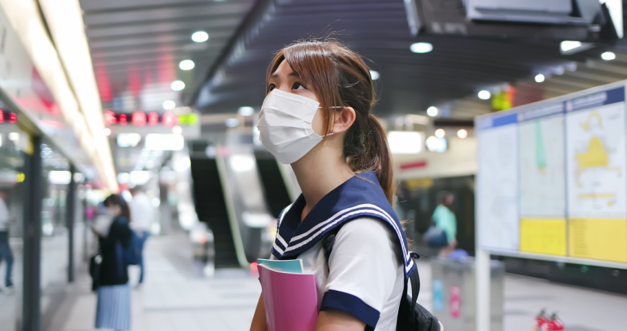 Senior high school student girl wear face mask and keep social distancing in metro station | Shutterstock HD Video #1054729031