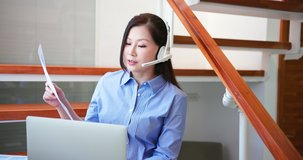 telework concept - Asian woman read financial report and use computer with headphone microphone to join a video meeting at home