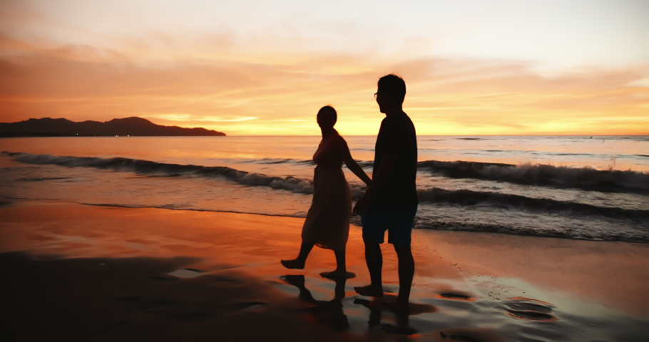 Silhouette of asian couple holding each other hands and walking on the beach during sunset