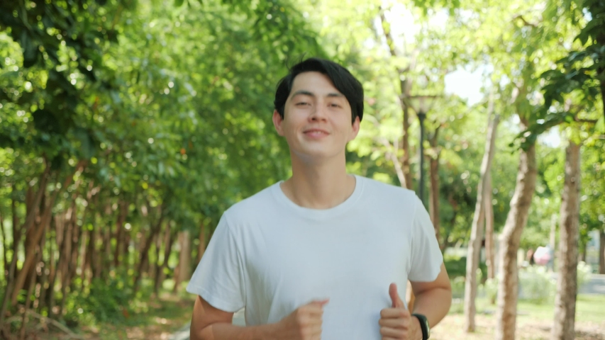 Happy handsome Asian man running in park on public green background, Fit man jogging at outdoor workout on background of trees. Healthy lifestyle concept. Slow motion Royalty-Free Stock Footage #1054729376
