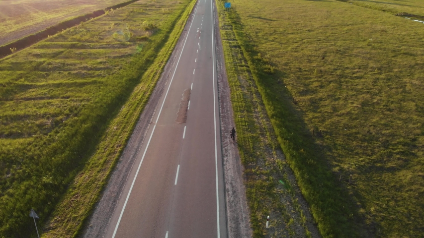 Aerial shot: single man riding bicycle by roadside. Sunset summer time. 4K