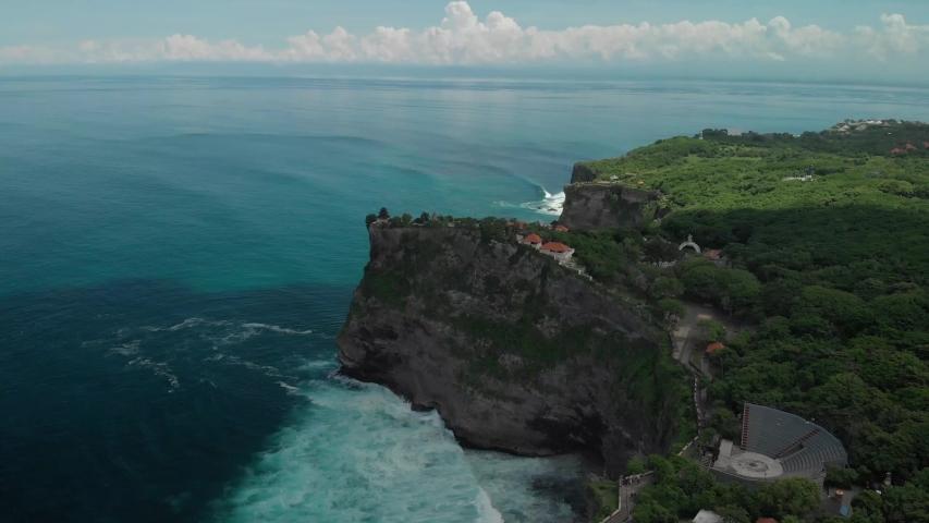 Aerial view of the impressive limestone cliffs in uluwatu, bali island, indonesia. Lots of green trees, waves and beautiful blue sea | Shutterstock HD Video #1054729931
