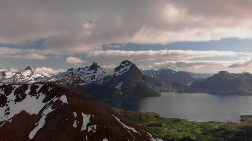 Aerial drone push in of panorama mountain view of Helgeland in northern Norway at golden hour | Shutterstock HD Video #1054729997