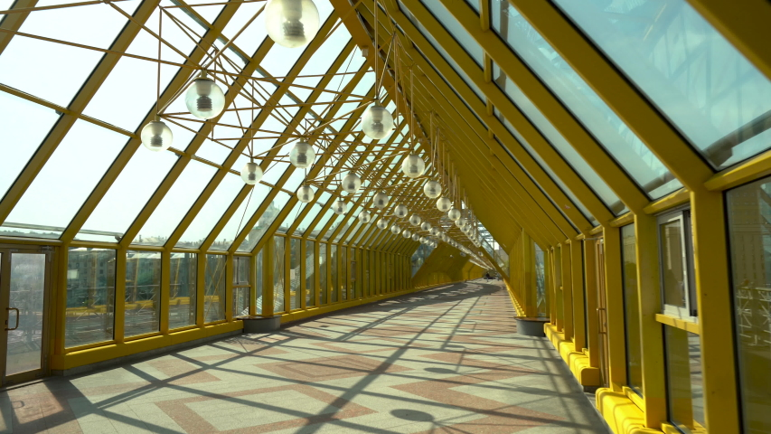 Empty long glass tunnel on the pedestrian bridge of yellow color with a panoramic glass roof . The camera is in motion. A bright Sunny day | Shutterstock HD Video #1054730039