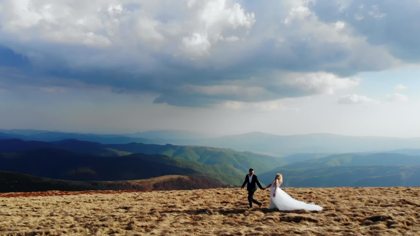 Wedding couple bride and groom holding hands walking against the backdrop of amazing mountains and dramatic sky. Aerial view. Attractive blonde and brutal chat. In love and happy | Shutterstock HD Video #1054730270