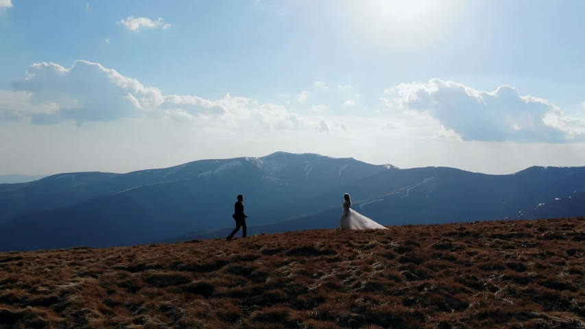 Silhouette of the bride goes to the groom, the wedding couple runs up to each other, on top of the mountain, with landscapes of amazing nature. Blue sky and rocks, aerial view | Shutterstock HD Video #1054730282