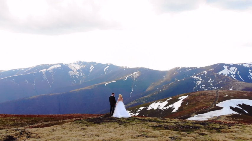 Amazing aerial view, the bride approaches the groom. in a white wedding dress. standing on a background of beautiful mountains landscape. Wedding couple hugging and kissing. top of snow covered rock.