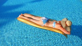 Young Caucasian model girl beige straw hat with wide brim, bathing suit, swims in outdoor pool, gold mattress, has rest, relaxes, rows her hands. Spa, vacation, relaxation. Tan. Slow motion video.