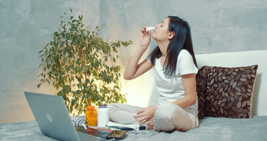 Young sick woman using nasal spray and paper handkerchief during a cold or allergy at home. | Shutterstock HD Video #1054730390