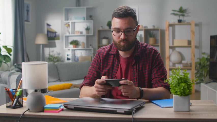 Happy man is playing video game at home using modern smartphone | Shutterstock HD Video #1054730417