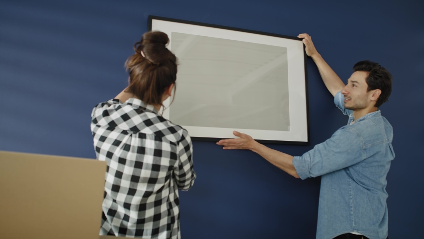 Video of couple hanging a picture frame on the wall. Shot with RED helium camera in 8K   Shutterstock HD Video #1054730531