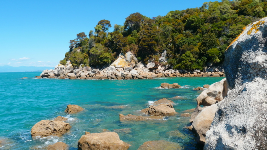 Loved for its turquoise water and golden sand beach, the sunny town of Kaiteriteri is a launching place for trips into the Abel Tasman National Park.   Shutterstock HD Video #1054731074
