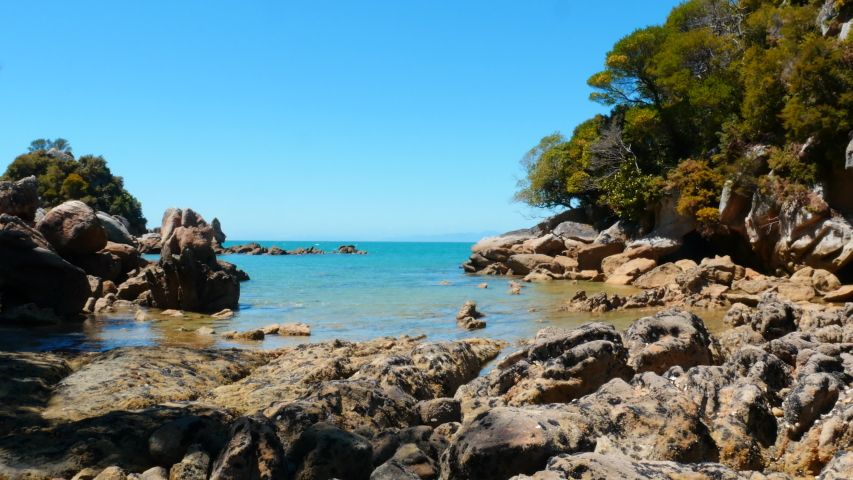 Loved for its turquoise water and golden sand beach, the sunny town of Kaiteriteri is a launching place for trips into the Abel Tasman National Park.   Shutterstock HD Video #1054731077