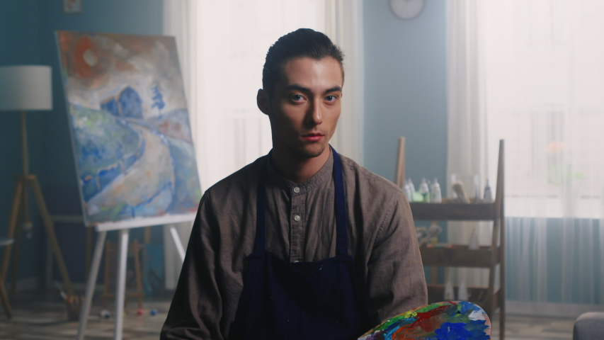 Portrait of young man, artist, sitting on a stool in studio, in working apron, holding palette with colorful paints in his hand, canvas and painting tools are on the background, Zoom out, Slow motion.