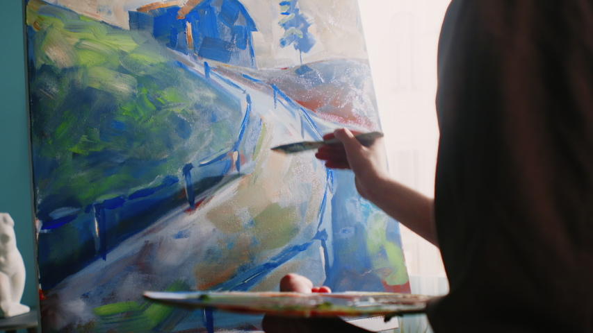Young artist is working in his inspiring home studio, creating a new artwork, using bright acrylic paints, preferring contrast colors, enjoying the process of painting, Slow motion.