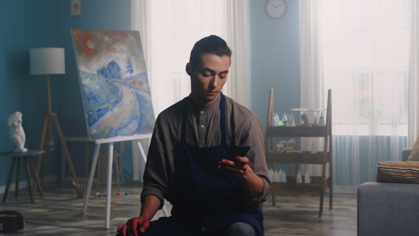 Portrait of young artist man sitting on a stool in apron and using his mobile phone, gadget, creative bright studio, canvas, tools, and elements of decor are on the background, Zoom In, Slow motion. | Shutterstock HD Video #1054731788