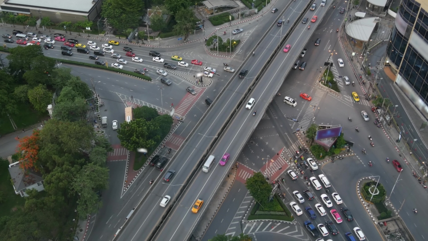 Traffic on crossroad on street. From above modern cars and motorcycles driving on intersection on street in center of Bangkok, Thailand. | Shutterstock HD Video #1054731866