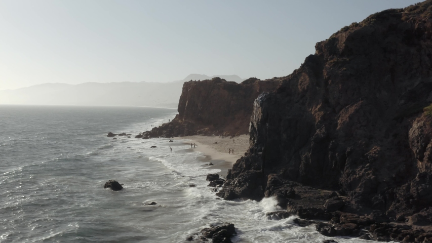 Aerial orbit shot of waves washing up on the Point Dume beach in Malibu sunset