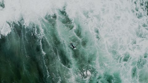 Brave and fearless cold water surfer athlete swim through big powerful waves, paddle to get to perfect surfing location point. Concept beauty and peace in sport in wild nature