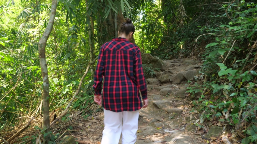 Young woman wearing bright red checkered shirt walks in lush tropical rainforest on sunny day close backside view | Shutterstock HD Video #1054732526