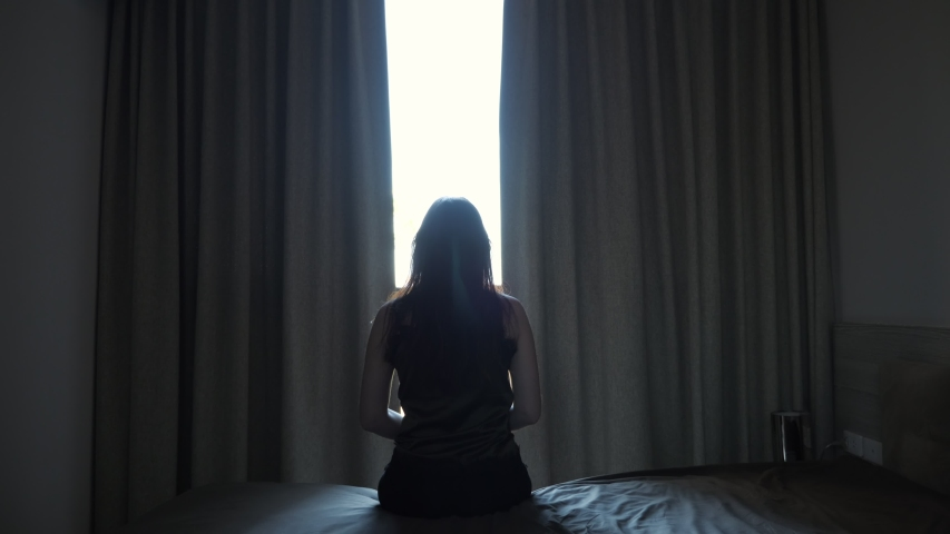 Long haired woman silhouette stretches hands sitting on bed against gap between window curtains in hotel room backside view | Shutterstock HD Video #1054732556