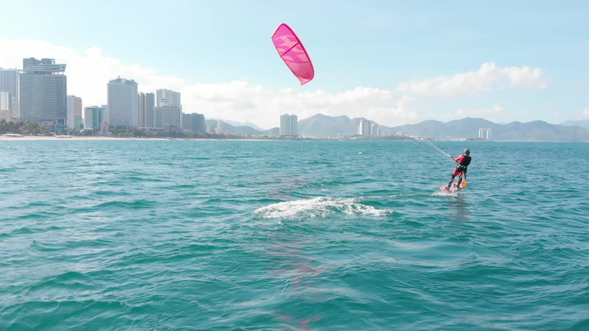 Aerial view of the city beach and active people practicing kite surfing and windsurfing. Kitesurfing place, sports concept, healthy lifestyle, human flight.