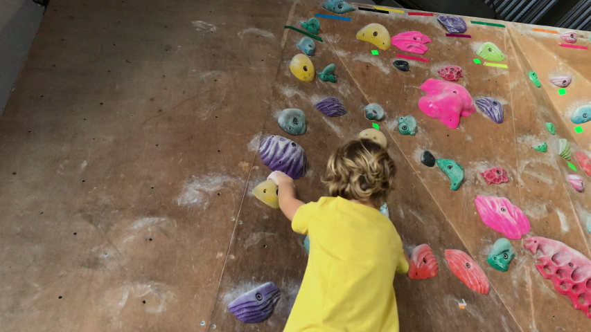 A little boy climbs up the wall in a bouldering gym. Shot on a phone | Shutterstock HD Video #1054732748