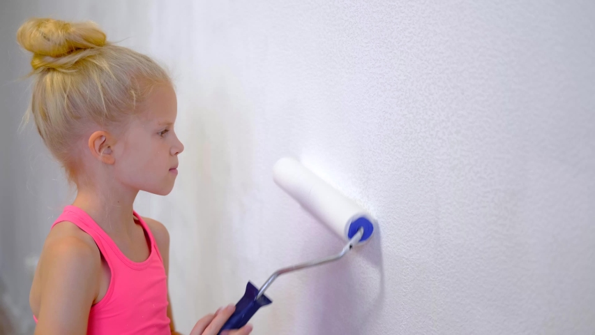 4k. blonde girl making repairs at home painting paint roller wall white paint. Renovation, family interior