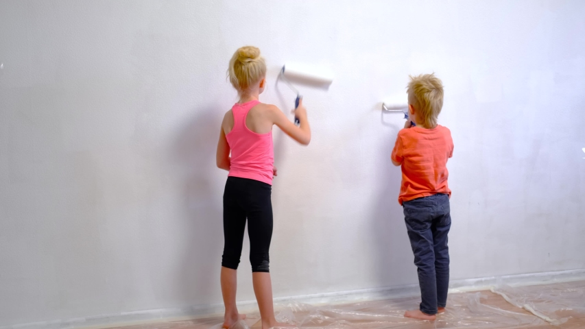 4k. blonde boy and girl making repairs at home, brother and sister painting paint roller wall white paint. Renovation, family interior