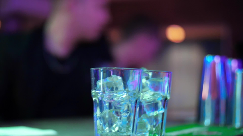 Bartender pouring transparent alcoholic drink  from a bottle into shot glasses. Closeup. Set of several glasses with cocktails. Barman pouring drinks into glasses for drinking.  | Shutterstock HD Video #1054732868