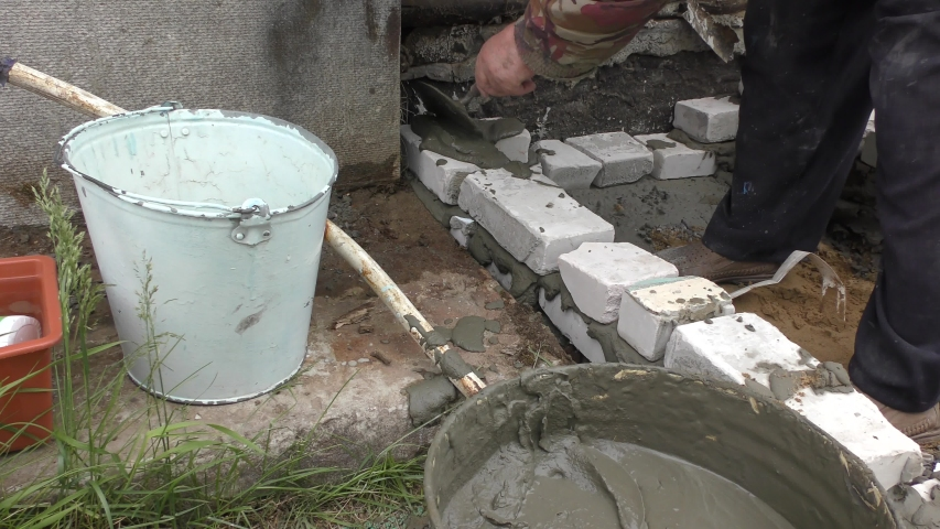 The Builder-bricklayer is laying bricks on cement mortar | Shutterstock HD Video #1054732964