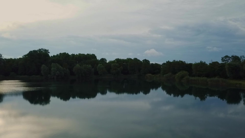 Flying backwards slowly over lake at sunrise with some lake grass and reeds showing. | Shutterstock HD Video #1054733342