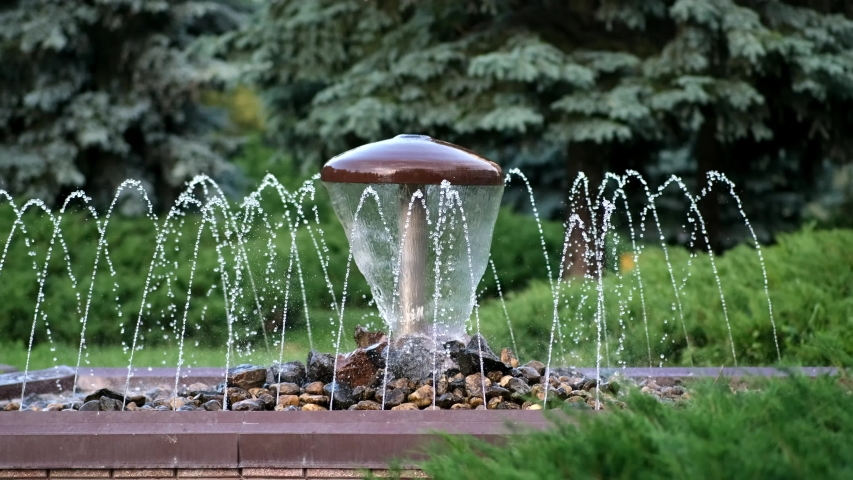 Decorative mushroom fountain with trickles on the background of greenery in the city Park.