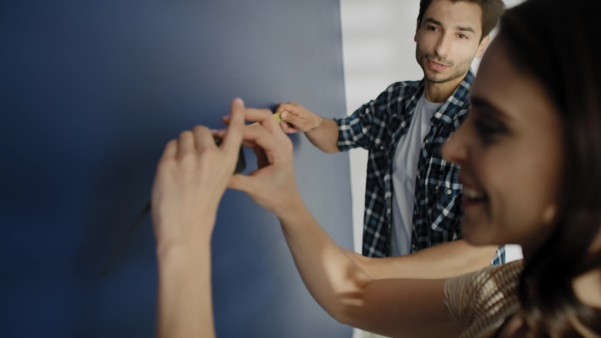 Video of couple taking measure on the blue wall. Shot with RED helium camera in 8K | Shutterstock HD Video #1054733750