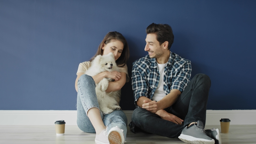 Zoom out video of couple with dog in empty house. Shot with RED helium camera in 8K | Shutterstock HD Video #1054733762